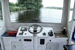 Bridge of small river ferry boat with black steering wheel and orange payment terminal
