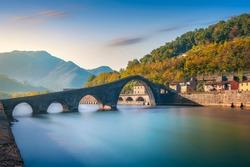 Bridge of the Devil or Ponte della Maddalena historic landmark in Garfagnana. Serchio river. Borgo a Mozzano, Lucca. Tuscany, Italy. Long Exposure in autumn.