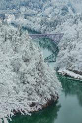 Bridge on a river with snow mountain as background in Tadami, Fukushima, Japan.