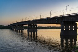 Bridge over a large river at sunset when the moon is visible in the sky