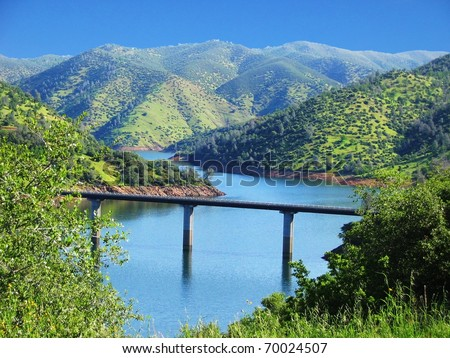 Bridge Over a River Surrounded by green hills at Yosemite National Park - stock photo