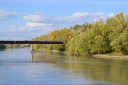 Bridge over the river. Autumn leaves on poplars along the river bank