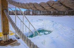 Bridge over the river surrounded by rope. Ice-hole for winter swimming.