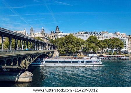 Bridge Pont Bir Hakeim and tourist boat tour on Seine river under dramatic sky #1142090912