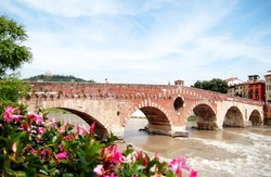 Bridge Ponte Pietra in Verona on Adige river. Veneto region. Italy. Sunny summer day panorama and blue sky with clouds. Santuario della Madonna di Lourdes (Our Lady of Lourdes sanctuary) on the hills