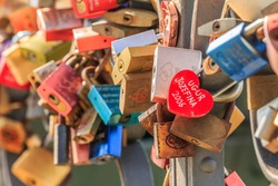 Bridge railing in Frankfurt with locks of love. Heart-shaped lock in the foreground Red, gold and multicolored locks with lettering on a sunny day in spring