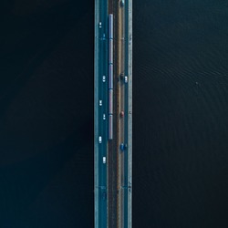 Bridge with two lanes and subway or train rails on a background of dark water. Metro bridge with moving cars. View from above. Aerial view