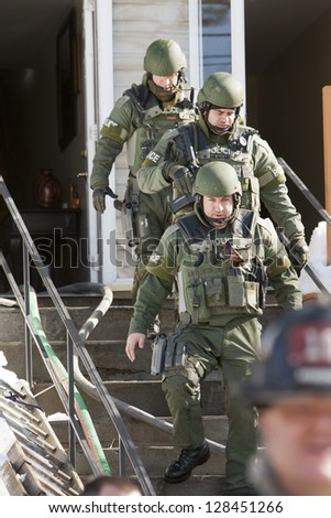 BRIDGEPORT, CT , U.S. -Â?Â? FEBRUARY 13 : Unidentified members of Bridgeport Police SWAT team exit a home after reports of a barricaded gunman in the residence on Roberts St. in Bridgeport, Ct. on February 13, 2013.