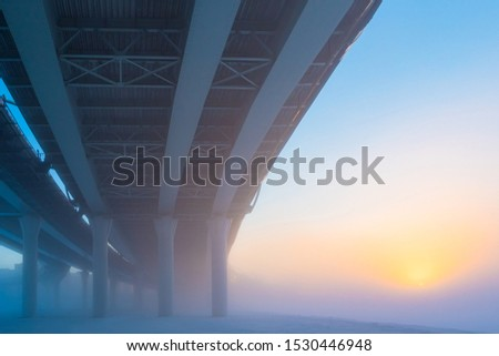Bridges. City architecture. The bridge on the fon of dawn. The construction of bridges. Road architecture. Expressways on the bridges. Bridge piers. Bridge on the background of the rising sun
