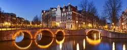 Bridges over a crossroads of canals in the city of Amsterdam, The Netherlands at night.