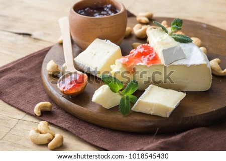 Brie Cheese delikatessen on rustic wood with rose jam,mint, french cuisine ingredients