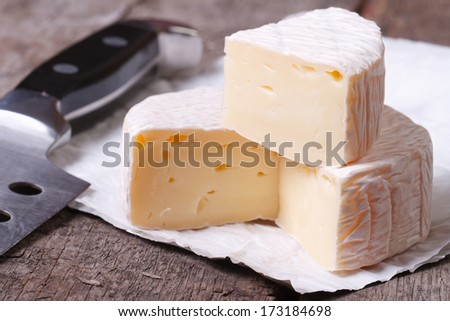 brie cheese on old wooden table and knife closeup