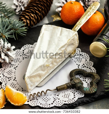 Brie cheese tangerines and fir twigs a bottle of wine and a corkscrew on a white Lacy napkin. Goodies for the holiday of Christmas and New year.