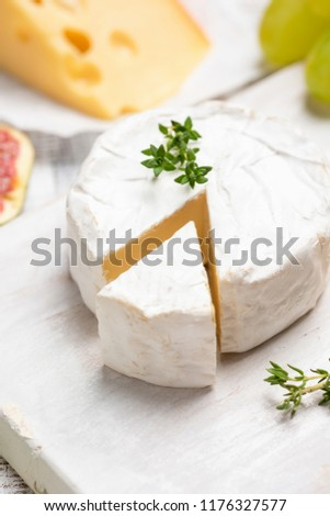 Brie or camembert cheese on white board. Closeup view, selective focus
