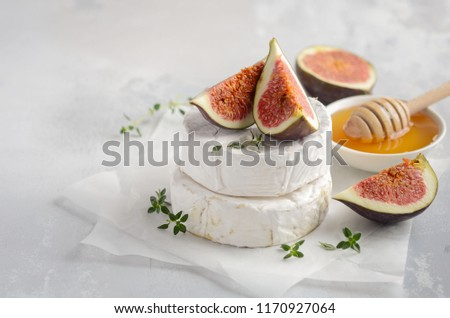 Brie or camembert cheese with figs, thyme, honey and nuts, selective focus.
