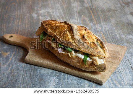Brie sanwdich in a French baguette, made of Brie de Meaux Cheese with some slices of rucola salad and chicken on a rustic wooden table. This sandwich, in France, is called sandwich au brie