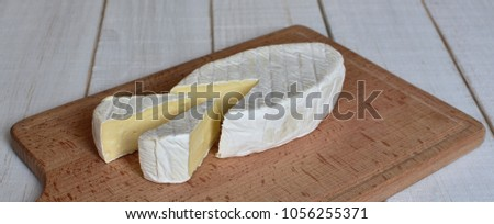 Brie type of cheese and two slices on the wooden cutting board. Camembert cheese. Fresh Brie cheese. Italian, French cheese.