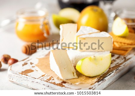 Brie type of cheese. Camembert cheese. Fresh Brie cheese and a slice on a wooden board with nuts, honey and apples. Italian, French cheese. Selective focus