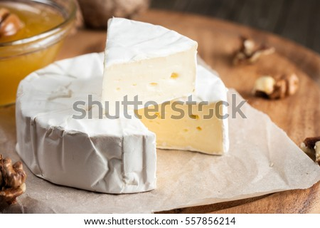 Brie type of cheese. Camembert cheese. Fresh Brie cheese and a slice on a wooden board with nuts, honey and leaves. Italian, French cheese. Сток-фото ©
