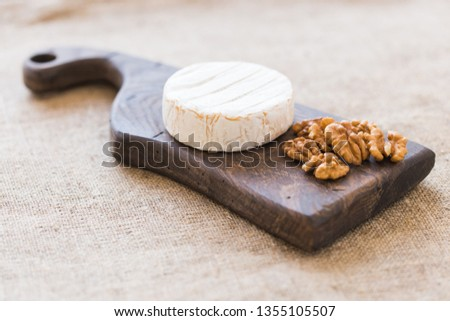 Brie type of cheese. Camembert cheese. Fresh Brie cheese on a wooden board with nuts and grapes. Italian, French cheese.