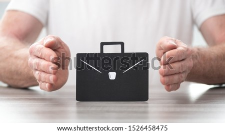 Briefcase protected by hands - Concept of job loss insurance