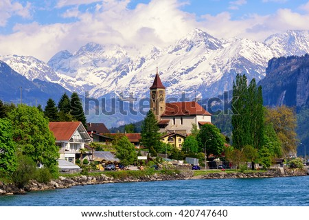 Brienz town on Lake Brienz by Interlaken, Switzerland, with snow covered Alps mountains in background #420747640