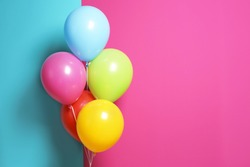 Bright air balloons for birthday party on color background