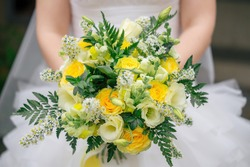 Bright and colorful autumn wedding bouquet with yellow roses, white lisianthus, chamomile and green fern leaves on the background of bride in white wedding dress