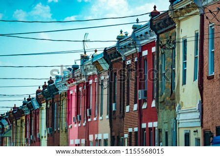 Bright and colorful brick row houses as seen from below in diagonal skyline view with power lines running across the street into their facades and a bright blue sky with white clouds behind