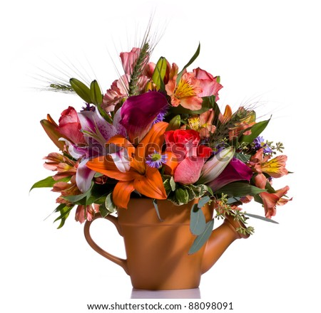 Bright and colorful bunch of flowers arranged in a watering can plant pot