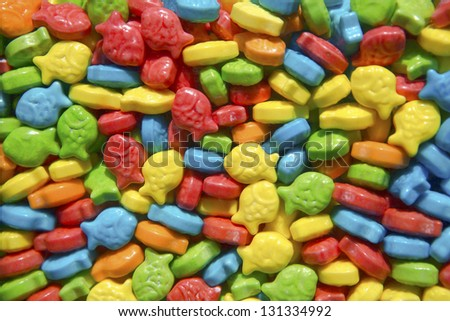 Bright and colorful fish shaped candies in a gumball dispenser.