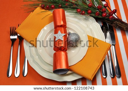 Bright and colorful Orange Christmas table setting with plates, forks and knives, and Christmas Cracker with decorations for a lively, stylish and fun holiday party atmosphere.