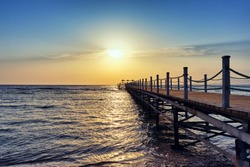Bright and colorful sunrise over the pier and sea. Perspective view of a wooden pier on the sea at sunrise with rocky islands in the distance