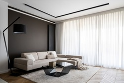 Bright and elegant living room with window wall behind curtains, stylish corner sofa and modern coffee table