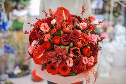 Bright and gorgeous bouquet of lovely red flowers in woman hands. No face, close up photo