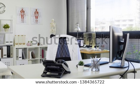 bright and modern medical doctor office complete with personal computer and telephone on desk white lab coat on chair. empty nobody in room in clinic. hospital workplace with sunshine through window.