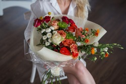 Bright and pretty bouquet of colorful, beautiful flowers in woman hands on the blurred background