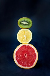 Bright and ripe round cytruses on a dark background. Fruits lemon, kiwi and grapefruit are arranged in the form of light-colored green, yellow, red. Healthy food. Vitamins.