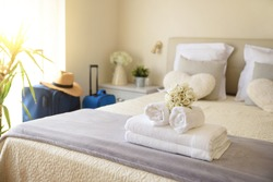 Bright and sunny vacation hotel room with suitcases and clean towel service on the bed