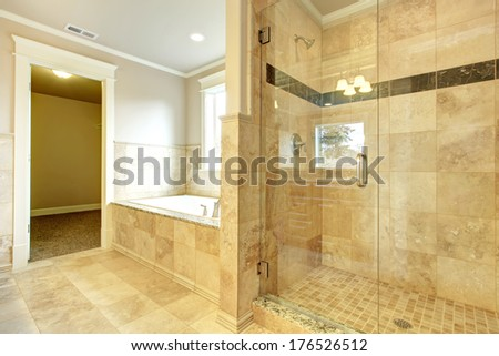 Bright and white bathroom with white tub, beige tile floor, glass door shower