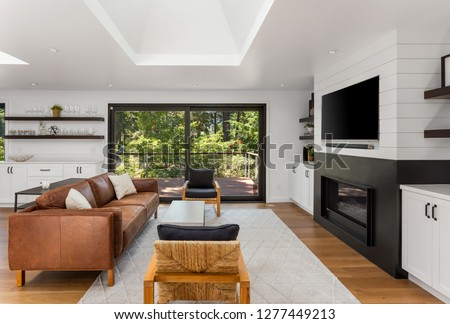 Bright and White Living Room with Fireplace in New Home. Features Hardwood Floors, Large Skylights and Sliding Glass Doors with Exterior View of Deck and Trees