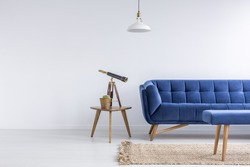 Bright apartment with blue sofa, bench, rug, lamp and table