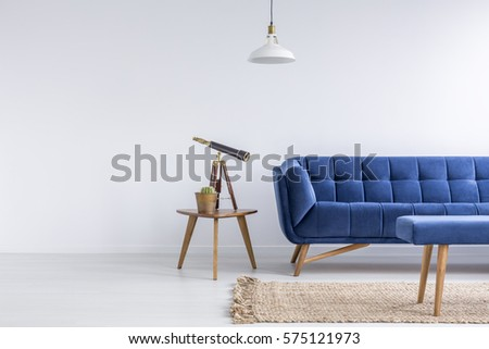 Bright apartment with blue sofa, bench, rug, lamp and table #575121973