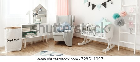 Bright armchair with blanket and cushion standing next to white wooden cradle in pastel baby room #728511097
