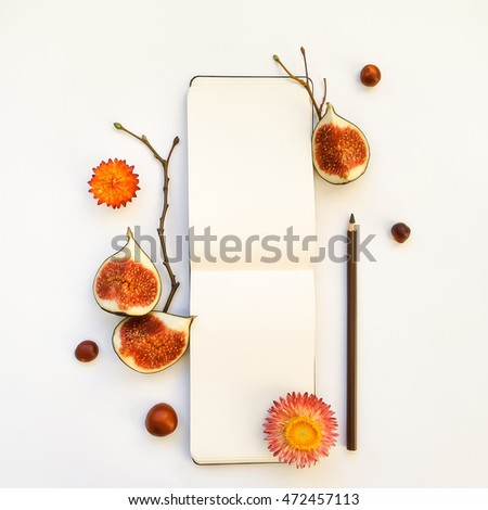 Bright autumn composition of a sketchbook, figs, chestnuts, dry flowers and tree branches on white background. Flat lay, top view