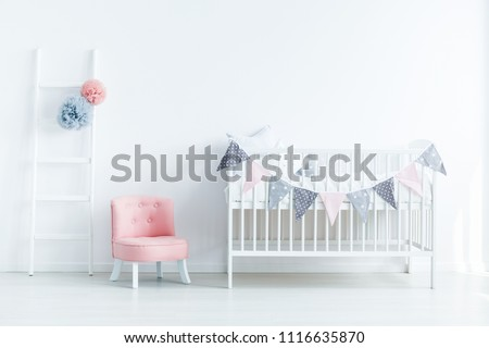Bright baby room interior with a crib decorated with triangles on a rope, pink seat and ladder with pompoms Foto stock ©
