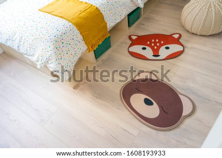 Bright baby room with cute animal carpet on the floor.