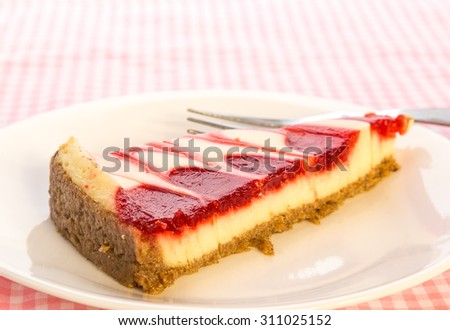 Bright back lighting on slice of strawberry swirl cheesecake on pink gingham tablecloth.