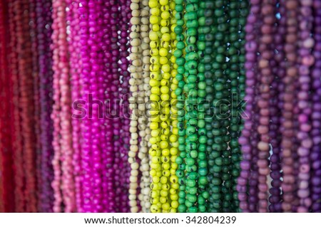 Bright background of handmade strands of colorful beads at outdoor crafts market in Rio de Janeiro, Brazil