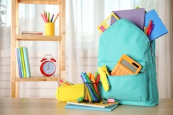 Bright backpack and school stationery on table indoors, space for text